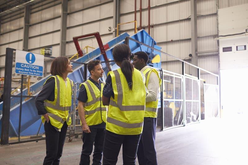 Vier medewerkers in bespreking in een industrieel binnenland royalty-vrije stock foto