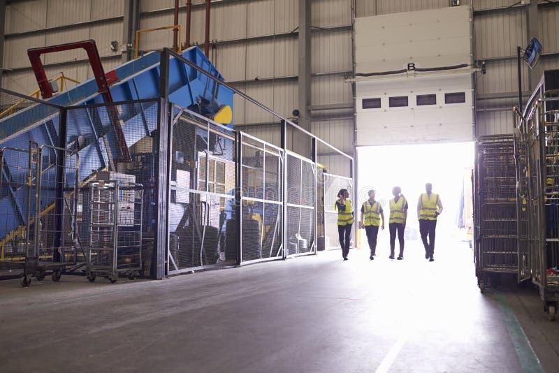 Vier medewerkers die in een industriële binnenlandse, brede mening lopen stock afbeeldingen