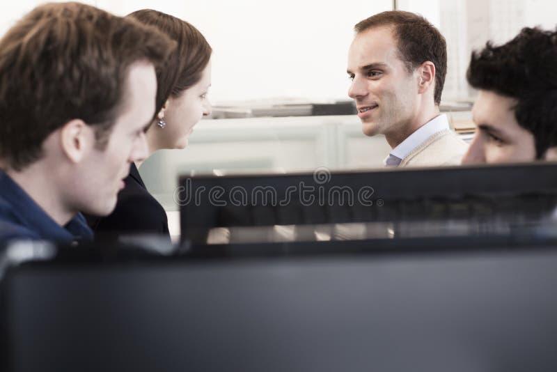 Vier medewerkers die en in het bureau door de computermonitors zitten bespreken stock foto