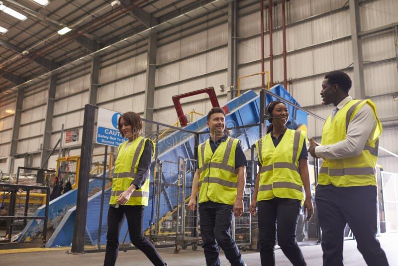 Vier medewerkers spreken aangezien zij in een industrieel binnenland lopen royalty-vrije stock afbeeldingen