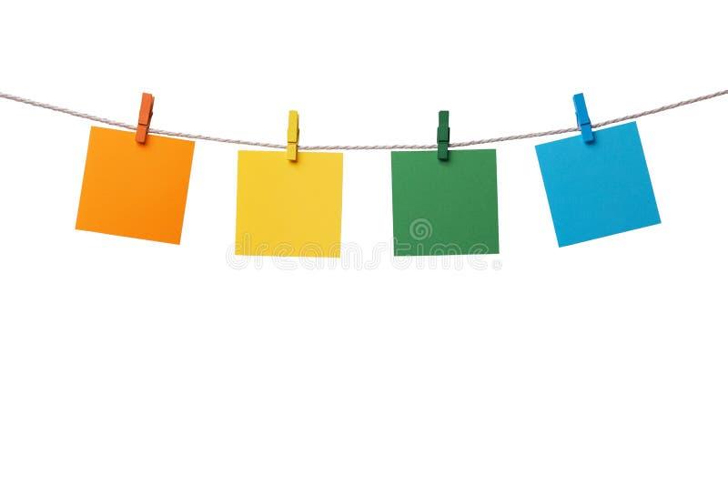 Vier mehrfarbige leere Papieranmerkungen, die am Seil mit den hölzernen Wäscheklammern lokalisiert auf Weiß hängen stockbilder