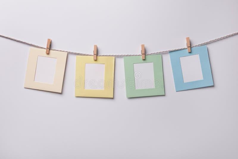 Vier mehrfarbige Papierfotorahmen, die am Seil auf weißem Hintergrund hängen lizenzfreie stockfotografie
