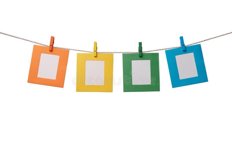 Vier mehrfarbige Papierfotorahmen, die am Seil mit den hölzernen Wäscheklammern lokalisiert auf Weiß hängen stockfoto