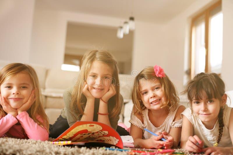 Vier meisjes die op de vloer liggen royalty-vrije stock fotografie