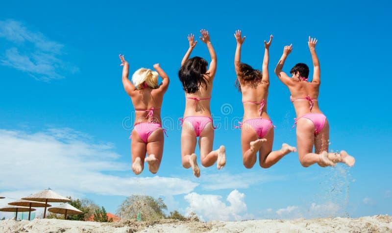 Vier meisjes die op het strand springen stock foto's