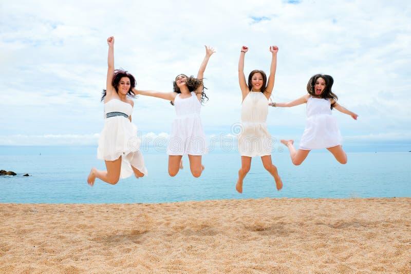 Vier meisjes die op strand springen royalty-vrije stock foto
