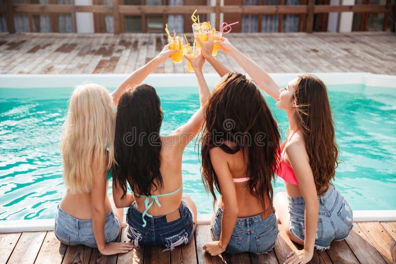 Vier meisjes die pret hebben en cocktails drinken bij zwembad royalty-vrije stock foto's