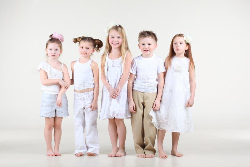 Vier meisjes en één jongen in witte kleren bevinden zich royalty-vrije stock foto's
