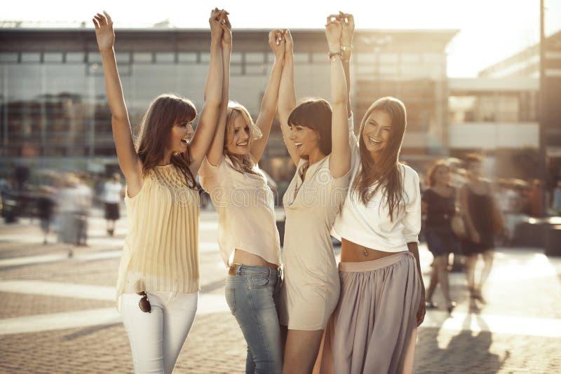 Vier meisjes in het zegevierende gebaar stock afbeelding