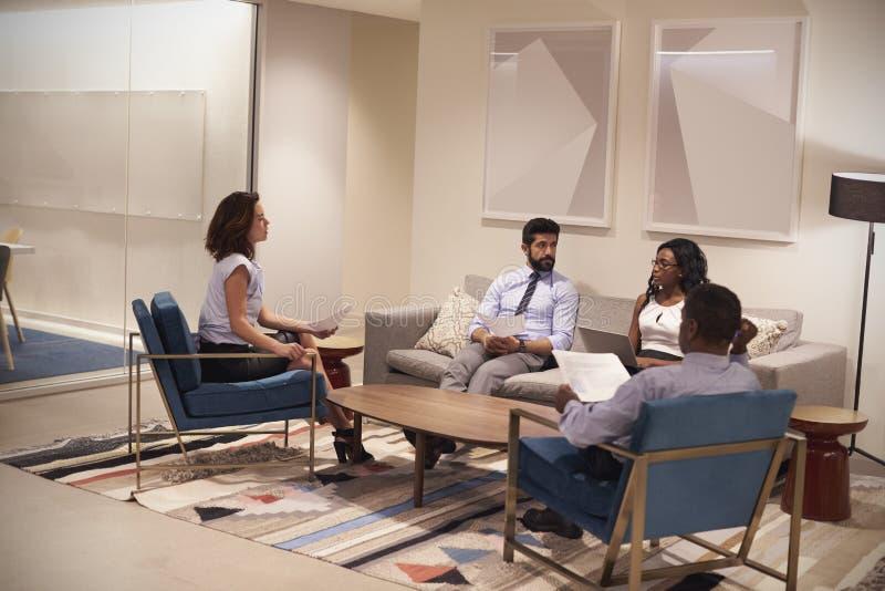 Vier mensen die op zitkamergebied samenkomen van collectieve zaken royalty-vrije stock fotografie