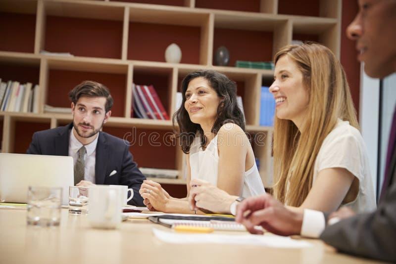 Vier mensen op een bedrijfsbestuurskamervergadering stock foto's