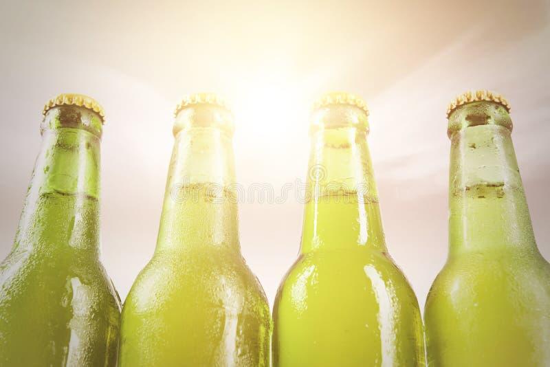 Vier met dauw bedekte flessen met vers bier stock afbeeldingen
