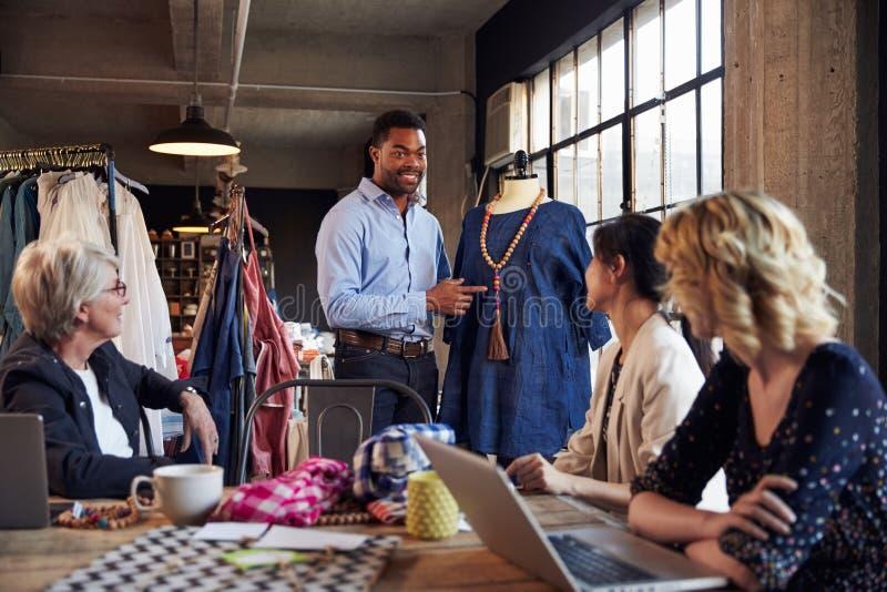 Vier Modedesigner in der Sitzung Kleid besprechend stockfotos