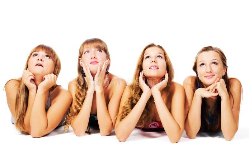 Vier mooie meisjes die op de vloer samen leggen royalty-vrije stock foto