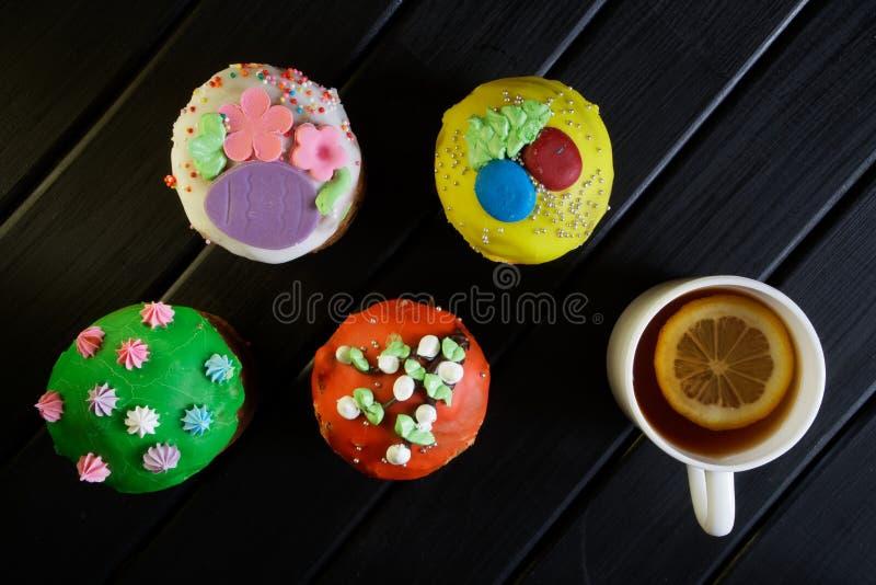 Vier multi-colored cupcakes - Pasen-cakes op een zwarte houten oppervlakte en een kop thee met een plak van citroen Het ontbijt v royalty-vrije stock foto