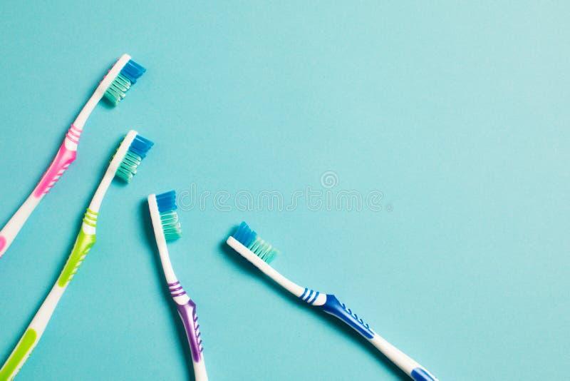 Vier multi-colored tandenborstels op een blauwe achtergrond royalty-vrije stock foto