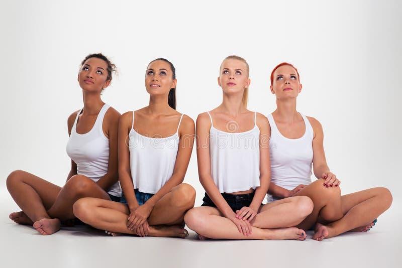Vier multi etnische vrouwen die op de vloer zitten royalty-vrije stock afbeelding