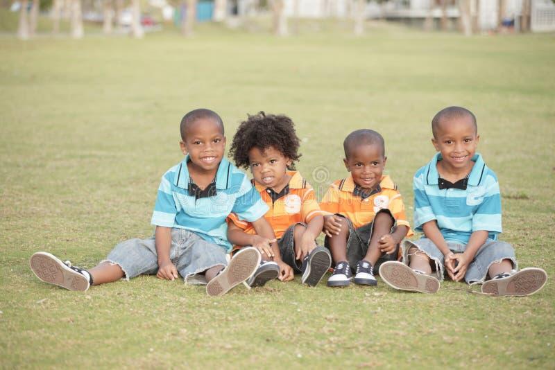 Vier nette Jungen im Park stockbild