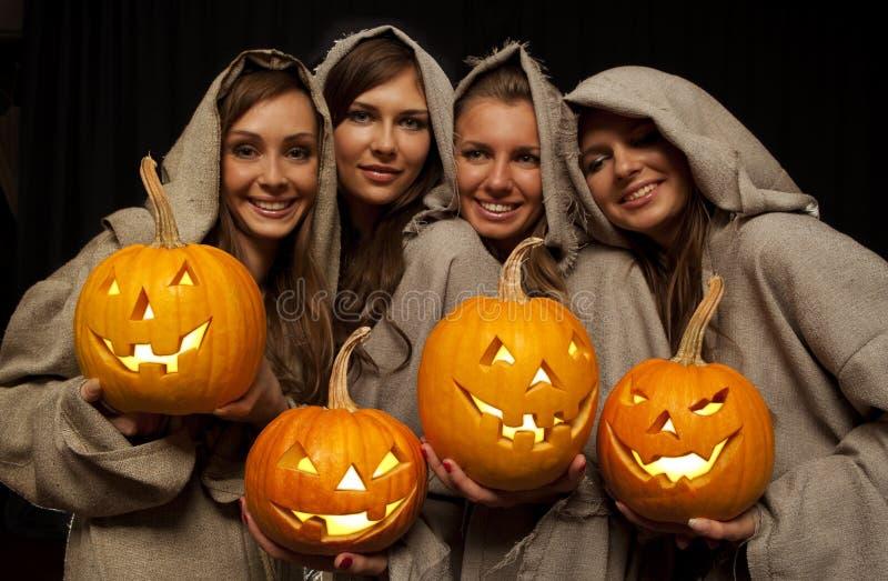 Vier Nonnen, die Halloween-Kürbise anhalten stockfoto
