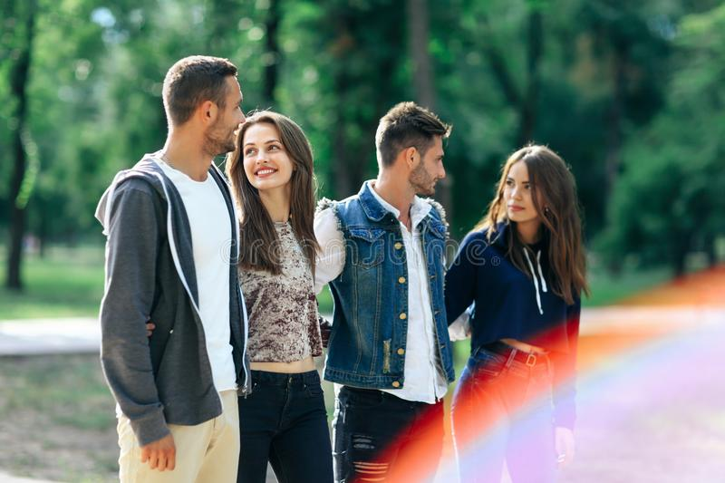 Vier onbezorgde jongeren die in park op zonnige dag lopen royalty-vrije stock foto