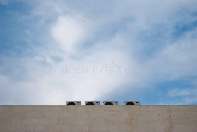 Vier openluchtairconditioningseenheden op een marmeren muur stock fotografie