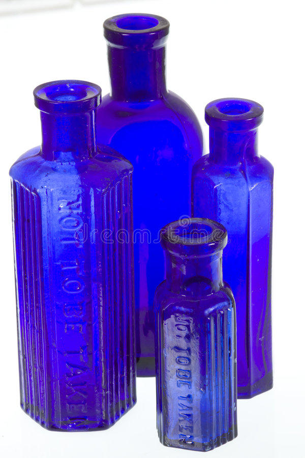 Vier oude blauwe flessen van de glasgeneeskunde royalty-vrije stock foto's