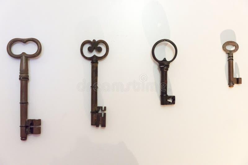 Vier oude roestige sleutels op de heldere muur royalty-vrije stock fotografie