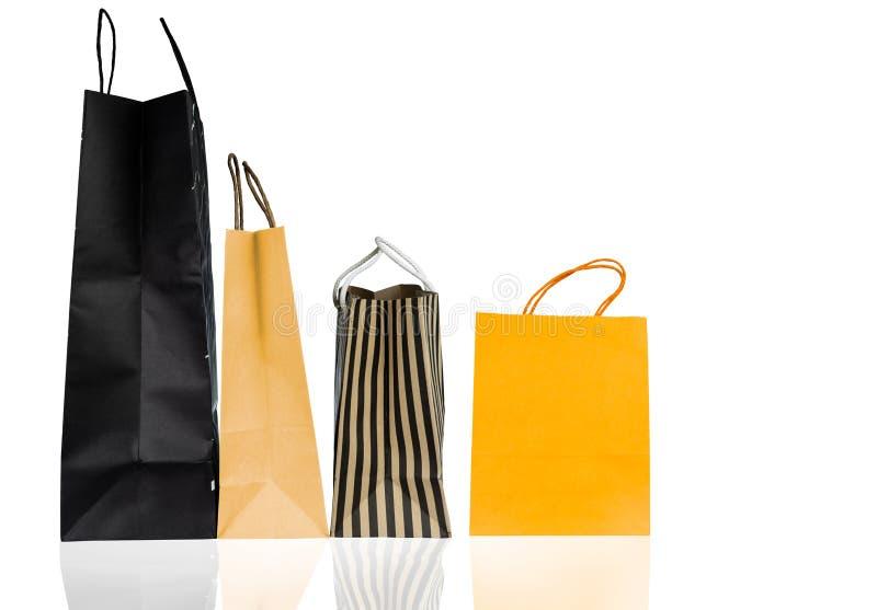 Vier Papiereinkaufstaschen lokalisiert auf weißem Hintergrund Einkaufstasche mit blauer, brauner und gelber Farbe Rabattverkaufsk lizenzfreie stockbilder