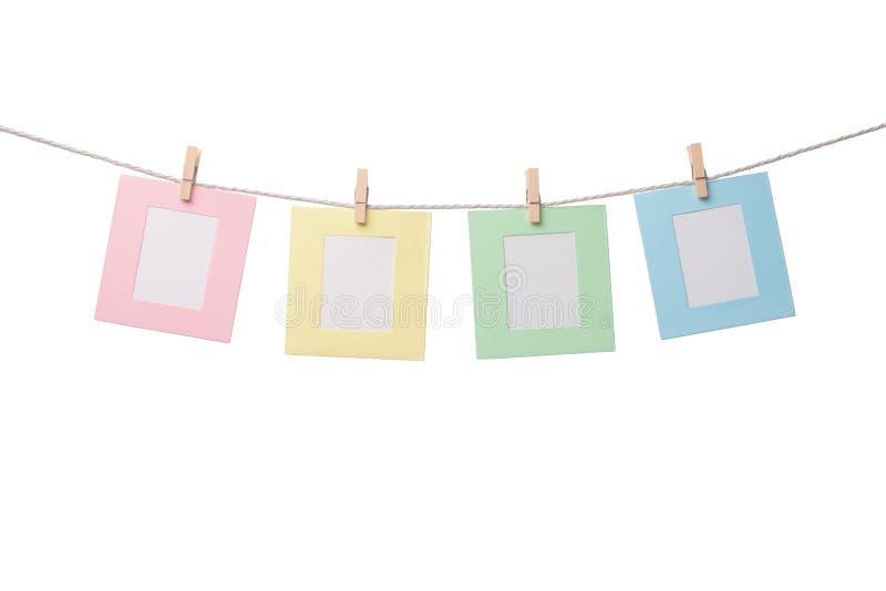 Vier Papierfotorahmen, die am Seil lokalisiert auf weißem Hintergrund hängen lizenzfreies stockfoto