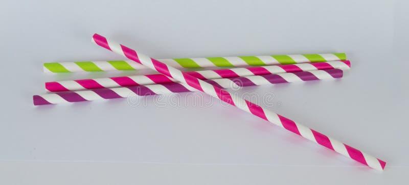 Vier Papierstrohe in einem horizontalen Format auf einem weißen Hintergrund stockfotografie