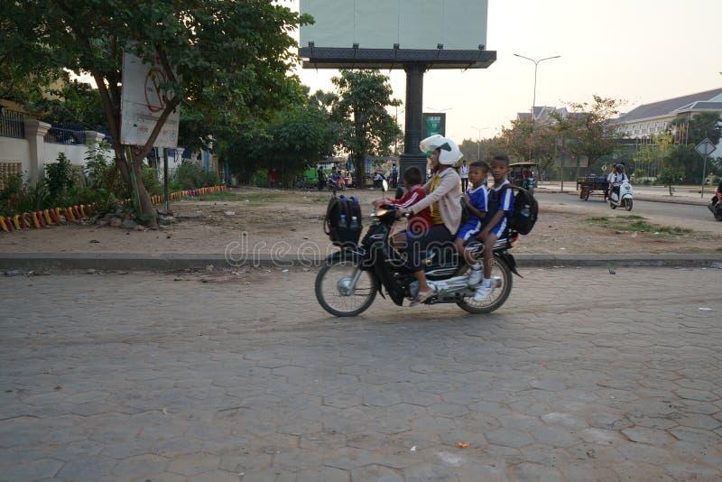 Vier personen die op één motorfietsrubriek berijden voor een school op Nationale Weg 6 in Siem oogsten, stock afbeeldingen