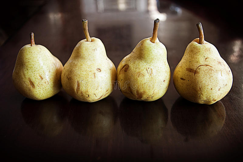 Vier reife Birnen in Folge stockfotos