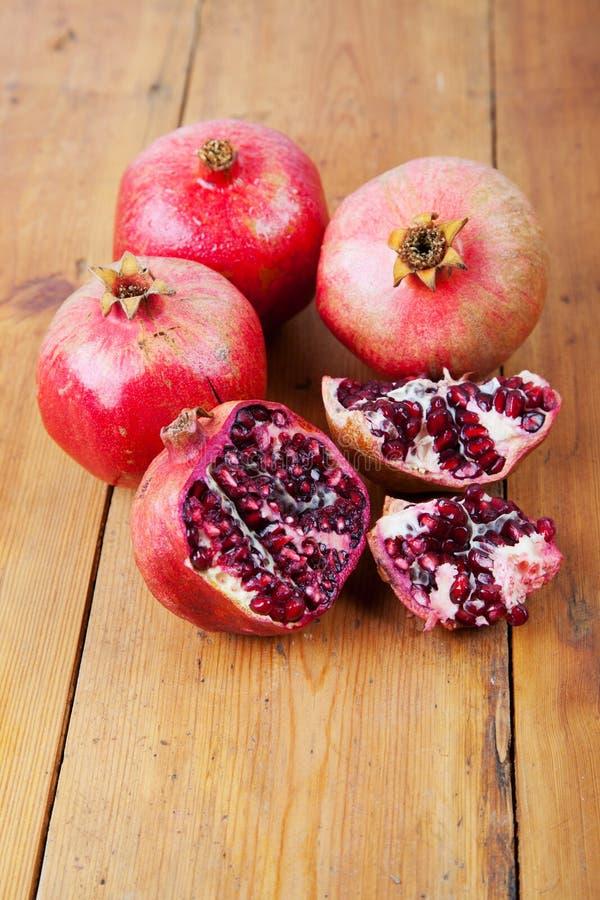 Vier rijp granaatappelfruit op houten oppervlakte stock fotografie