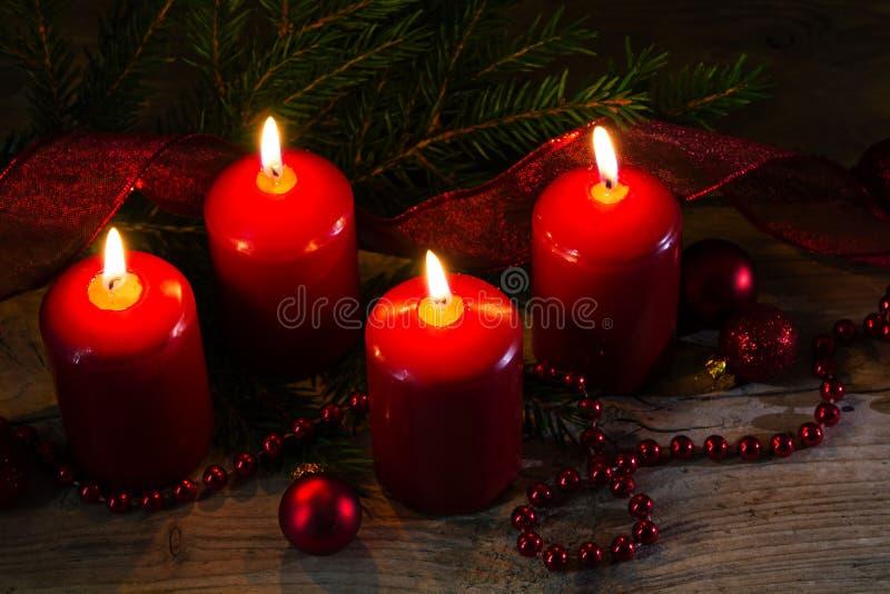 Vier rode brandende kaarsen bij de vierde komst, Kerstmis decorat stock foto