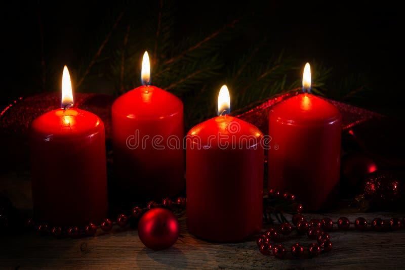 Vier rode brandende kaarsen bij de vierde komst, Kerstmis decorat stock fotografie