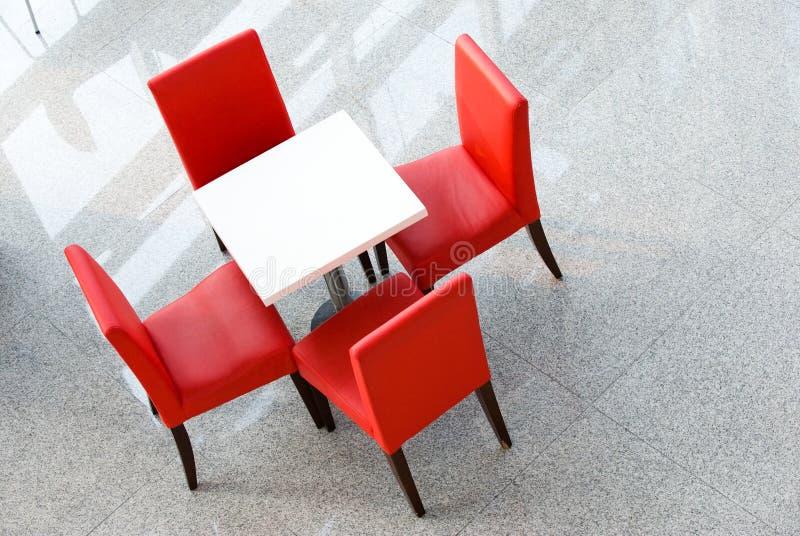 Vier rote Stühle an einem Tisch stockfotografie