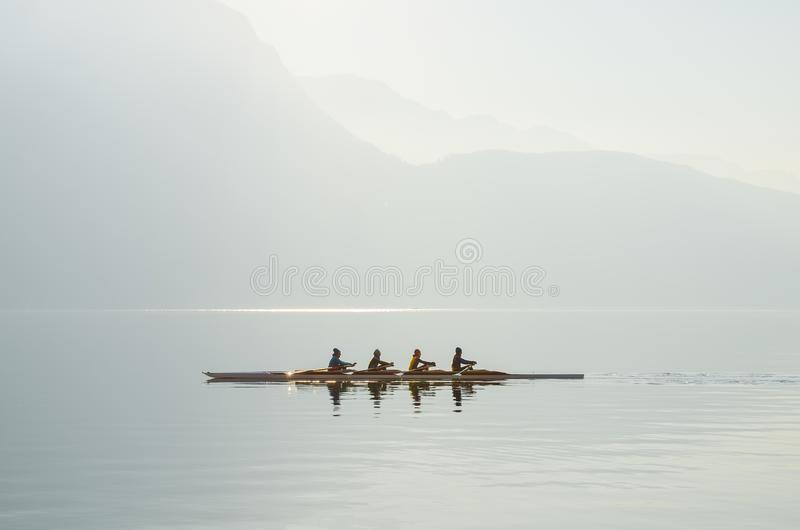 Vier Ruderer auf dem Boot, das auf sonnigen Morgen auf Hintergrund von Bergen auf See von Lugano schwimmt lizenzfreie stockbilder