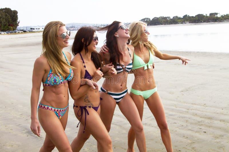 Vier schöne junge Frauen, die den Strand genießen lizenzfreie stockbilder