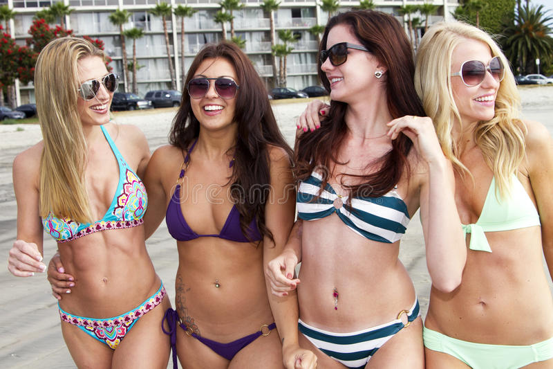 Vier schöne junge Frauen, die den Strand genießen stockbilder