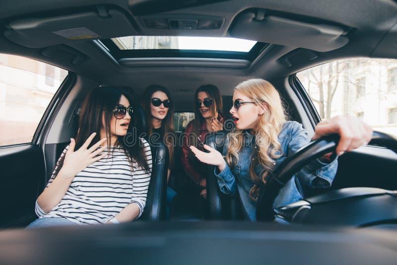 Vier schöne junge nette Frauen, die einander mit Lächeln beim Sitzen im Auto betrachten lizenzfreies stockbild