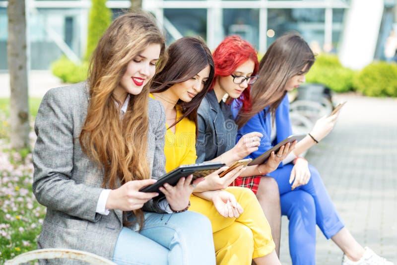 Vier schöne Mädchen mit Geräten sitzen auf der Bank Das Konzept des Internets, der sozialen Netzwerke, der Studie und des Lebenss stockfoto