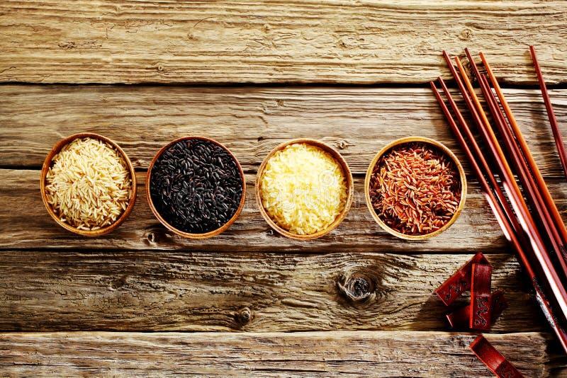 Vier Schüsseln unterschiedlicher Reis mit Essstäbchen stockbilder