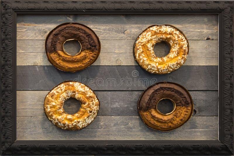 Vier Schaumgummiring-Kuchen in einem Rahmen, hölzerner Hintergrund lizenzfreie stockfotos