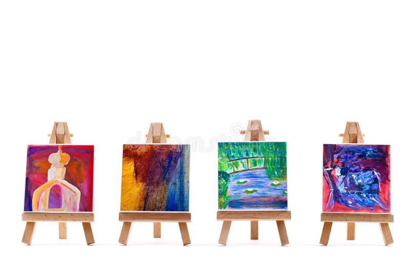 Vier schilderijen op schildersezels op wit royalty-vrije stock afbeelding