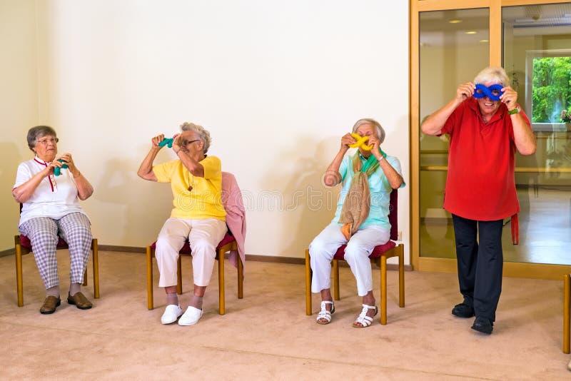 Vier Senioren, die Spaß während der Übungsklasse haben lizenzfreies stockfoto