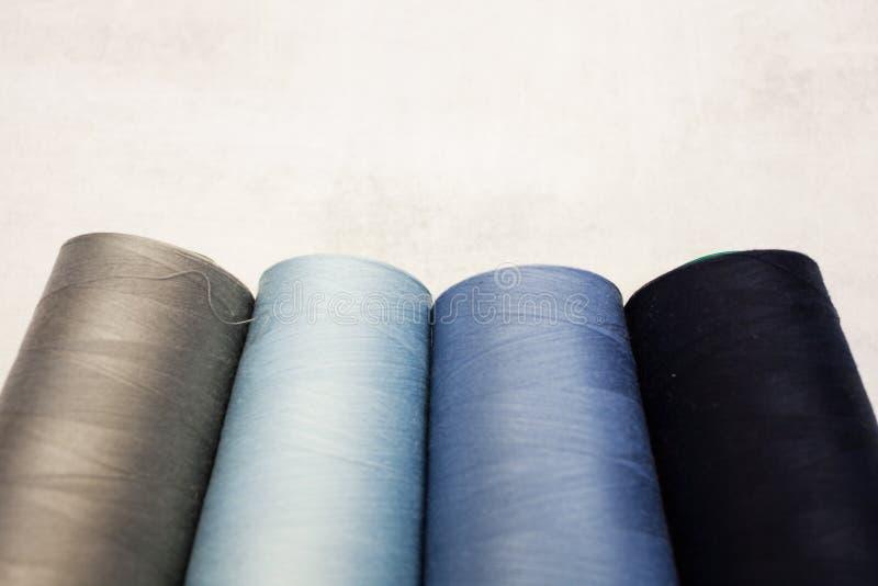 Vier spoelen van koude kleuren: grijs, blauw en lichtblauw Het naaien productie en huisambachten royalty-vrije stock foto's