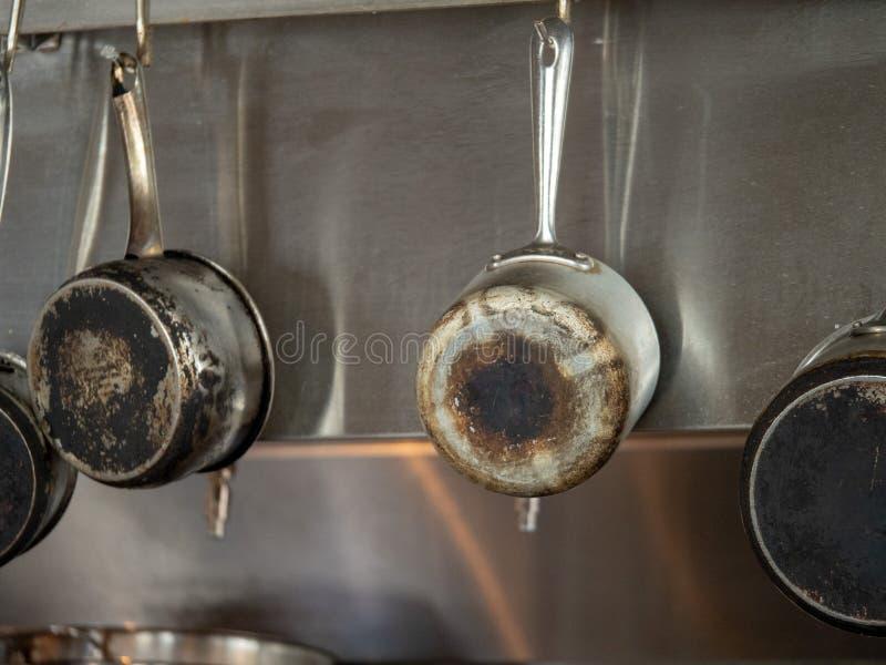 Vier Stahlkasserollen mit den gebrannten Unterseiten, die in der industriellen Küche hängen stockfoto
