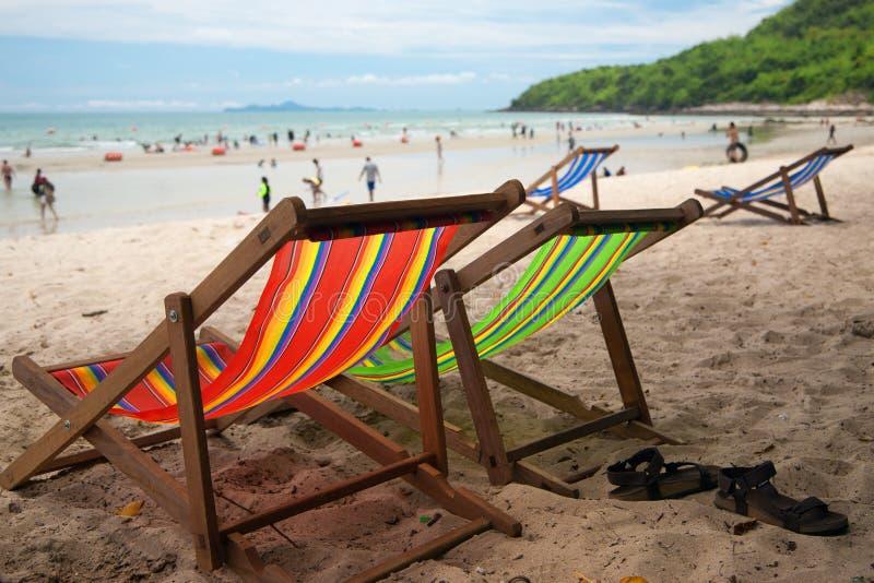 Vier strandleunstoel met leerpantoffels met toeristen op zandig strand stock fotografie