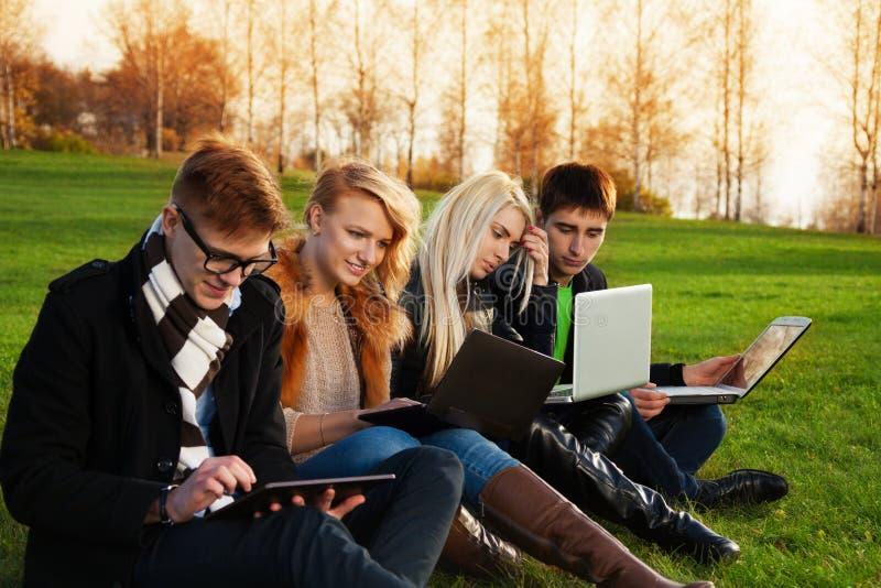 Vier studenten die aan laptops in het park werken royalty-vrije stock afbeelding