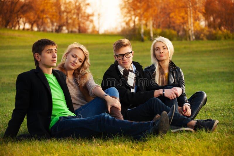 Vier Studenten, die auf dem Darlehen sitzen stockfotografie